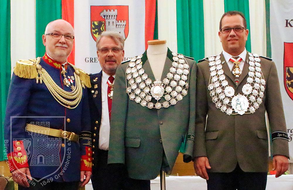 Oberst Joachim Schwedhelm und Präsident Dr. Peter Cemerius präsentieren die alte und die neue Kette des BSV gemeinsam mit König Dominik I. Wegener, der das neue Königssilber schon einmal probe trägt.